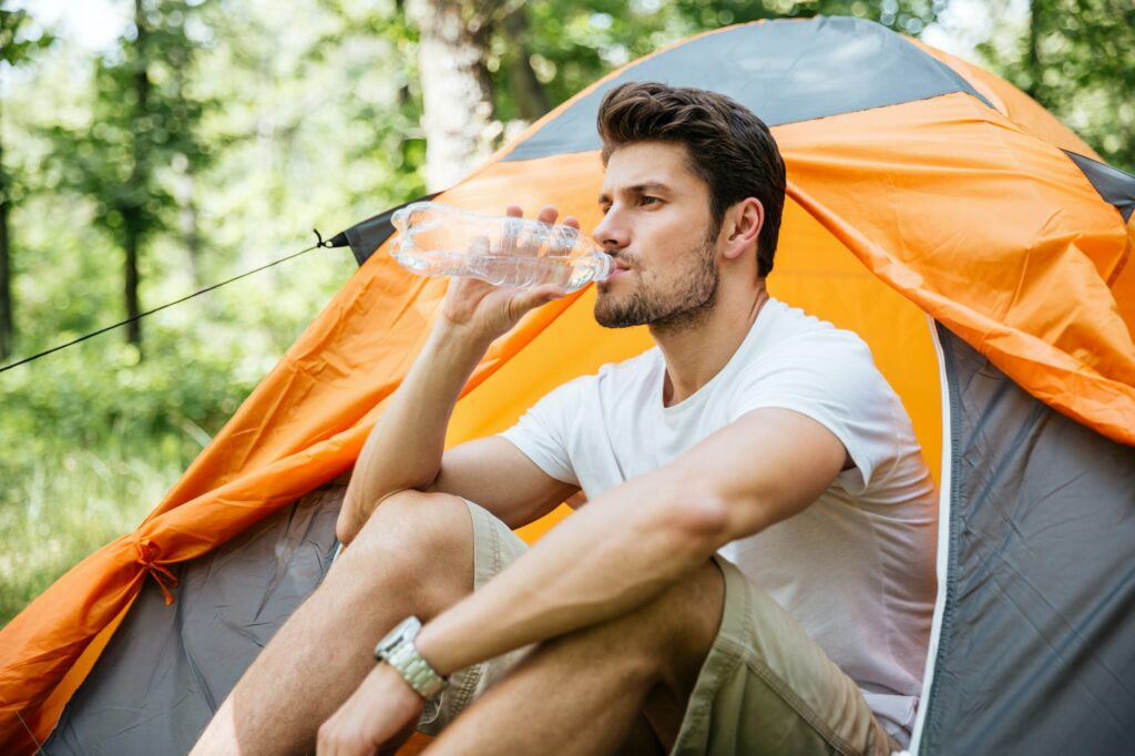 Man sitting near touristic tent and drinking water in forest